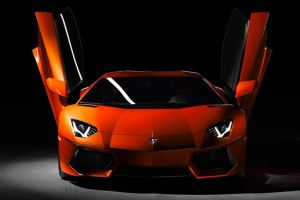 orange color Lamborghini Aventador with vertical doors open and headlights turned on